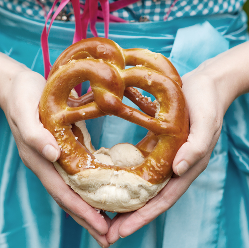 Oktoberfest pretzels in hands of a woman in traditional German clothes, blue bavarian dirndl. Bread as traditional food on fest